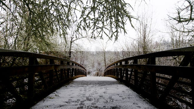 A bridge over the Willamette Slough in Minto-Brown Island Park is slippery with snow and slush on Wednesday, Jan. 11, 2017.
