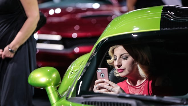 Sarah Dilworth of Plymouth takes a selfie in a 2017 Dodge Viper during the 2017 North American International Auto Show Charity Preview at Cobo Center in Detroit on Friday, January 13, 2017.