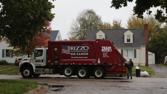 Rizzo Environmental Services workers pick up trash on Hastings St. in Flint in October 2016.
