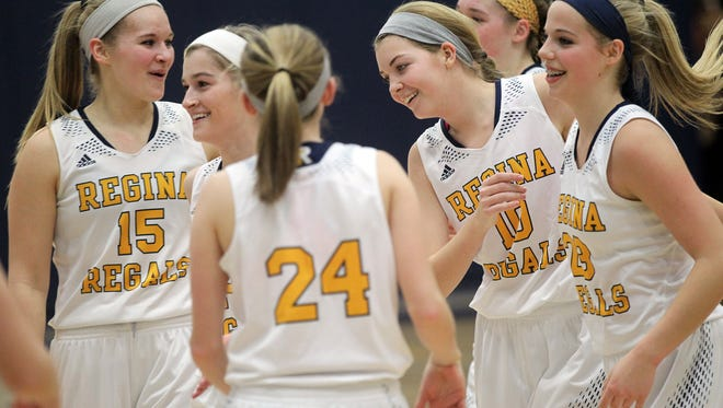 Regina teammates surround Alexa Lehman after her buzzer-beater to end the first quarter of their game against Mid-Prairie at Regina on Tuesday, Jan. 17, 2017.