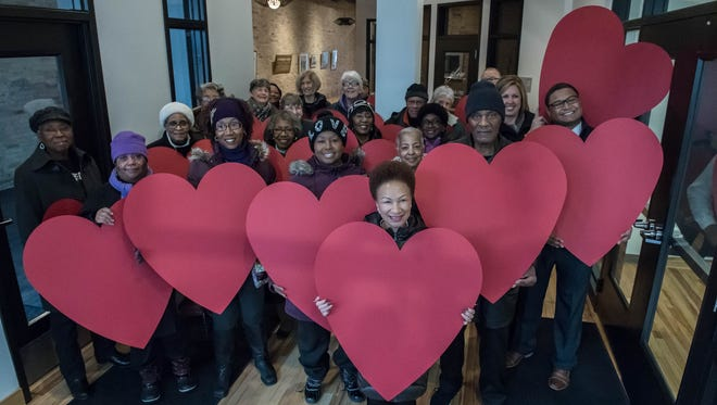 Participants gather with large heart cut outs at the Battle Creek Community Foundation for the National Day of Racial Healing on Tuesday.