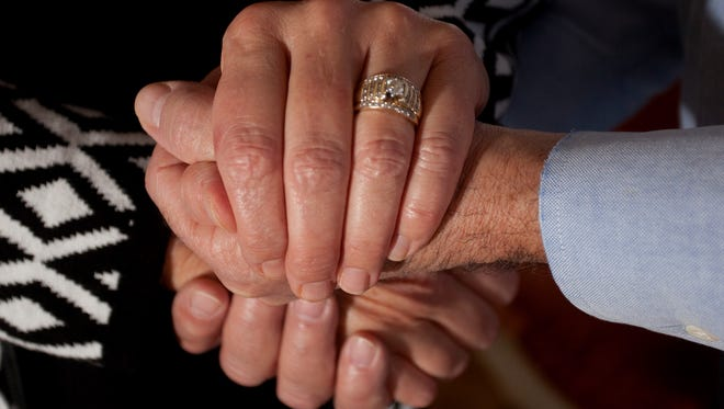 Phil and Cindi Shaftner pose with Cindi's wedding ring in their home in Lansing on Wednesday. Cindi's wedding ring was accidentally flushed down the toilet in 2015.