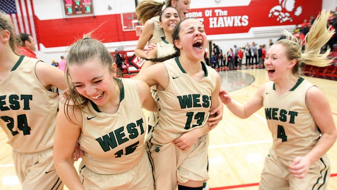 West High teammates celebrate their win over City High on Tuesday, Jan. 24, 2017.