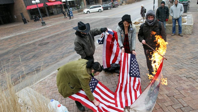 A group of protesters burns American flags on the pedestrian mall along Clinton Street in Iowa City, Iowa, on Thursday, Jan. 26, 2017.