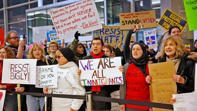 People chant slogans at the Indianapolis International Airport, Sunday, Jan. 29, 2017, during a protest against President Donald Trump's executive order temporarily suspending all immigration for citizens of seven majority Muslim countries for 90 days. (Kelly Wilkinson/The Indianapolis Star via AP)