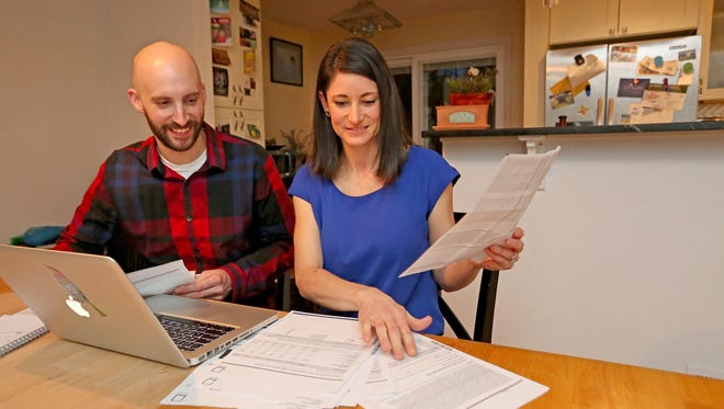 Jeff Whitehall and Kathryn Jacoby go over their budget at their home in Seattle's Crown Hill neighborhood.