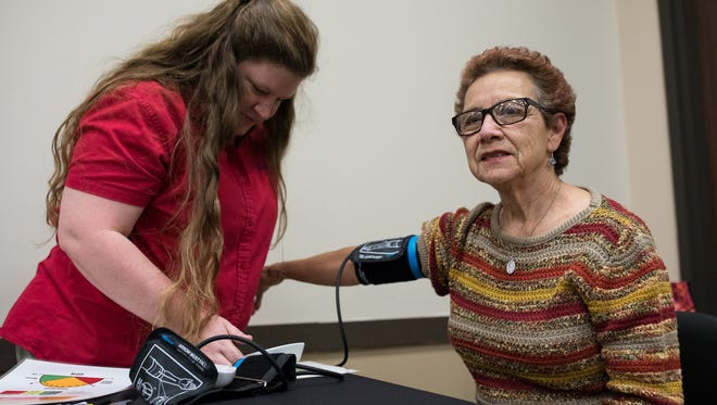 Keroy Belt of Davila takes Carlotta Narvaez's blood pressure at the Corpus Christi-Nueces County Public Health Department during the  American Heart Association's National Go Red for Women Campaign heath fair on Friday, Feb. 3, 2017.