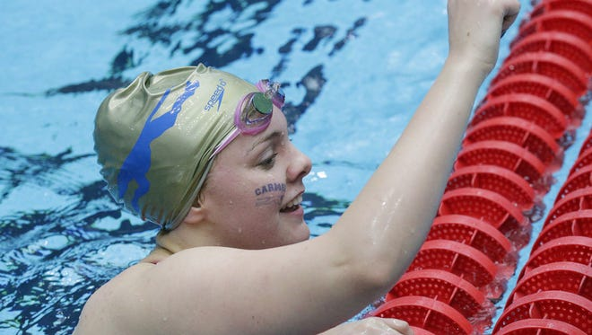 Carmel's Sammie Burchill raises her fist after competing in the girls 100 yard backstroke, during the IHSAA girls swimming state finals, held at IUPUI Natatorium, Feb. 11, 2017.