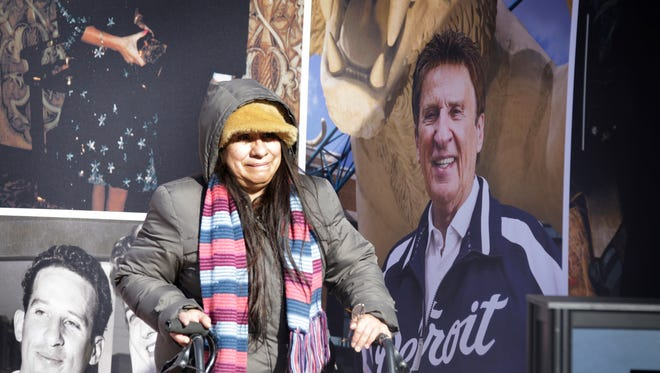 Elizabeth Banda, 63, of Detroit gets emotional at a wall commemorating Mike Ilitch that was set up outside of Comerica Park Monday, Feb. 13, 2017.