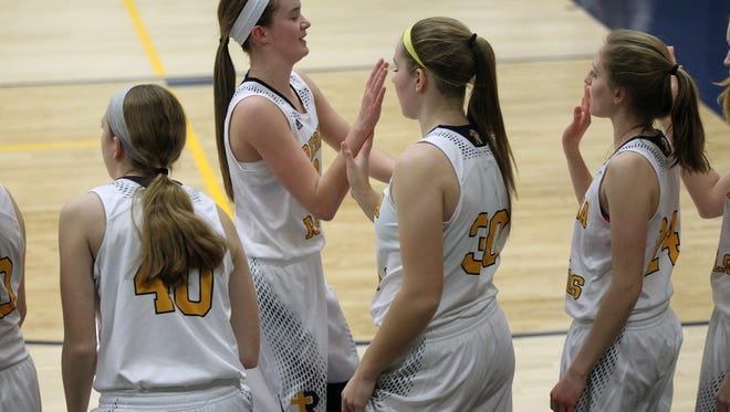 Regina's Mary Crompton high-five's teammates as she heads to the bench during the Regals' game against Tipton at Regina on Tuesday, Feb. 14, 2017.
