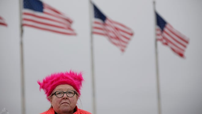 Virginia Keith, 62, of Waterville, N.Y., eats an orange in the shadow of the Washington Memorial after participating in the Women's March on Washington on Saturday, Jan. 21, 2017. Keith sewed over 1,000 pussy hats and sold them and gave some away.