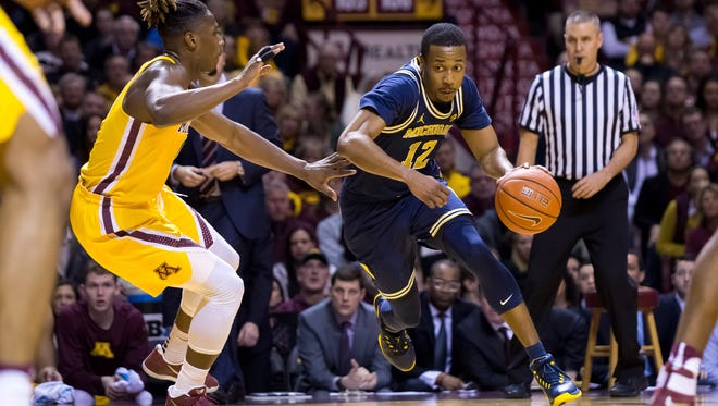 Michigan guard Muhammad-Ali Abdur-Rahkman (12) dribbles in the first half against Minnesota guard Akeem Springs (0) at Williams Arena Sunday.