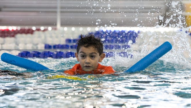 Third grader Isaiah Garza from Dawson Elementary School holds a kick board as he swims with a noodle in the pool at the Corpus Christi Natatorium on Wednesday, Feb. 22, 2017.