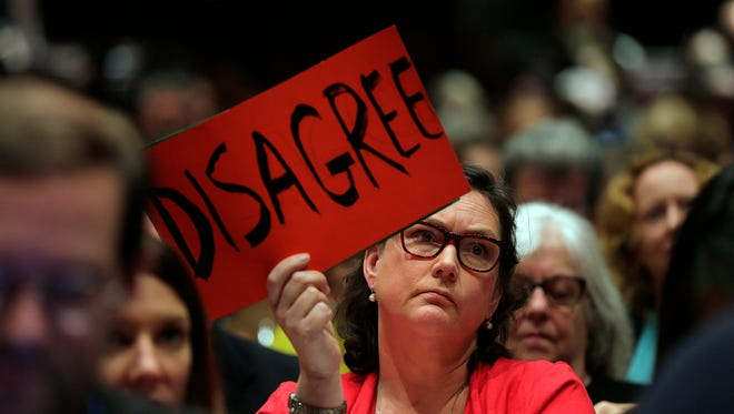 """Elizabeth Lewandowski holds a sign that reads """"disagree"""" as New Jersey Rep. Leonard Lance holds a town hall meeting at Raritan Valley Community College, Wednesday, Feb. 22, 2017, in Branchburg, N.J. (Tanya Breen/The Asbury Park Press via AP)"""