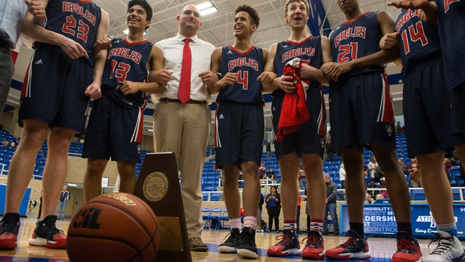 Veterans Memorial huddles around their trophy and game ball after winning the Region IV-5A final over Dripping Springs at Northside Sports Gym in San Antonio  on Saturday, March 4, 2017.