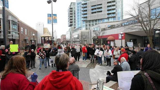A group of protesters gather on the pedestrian mall for a rally in support of worker rights on Wednesday, March 8, 2017.