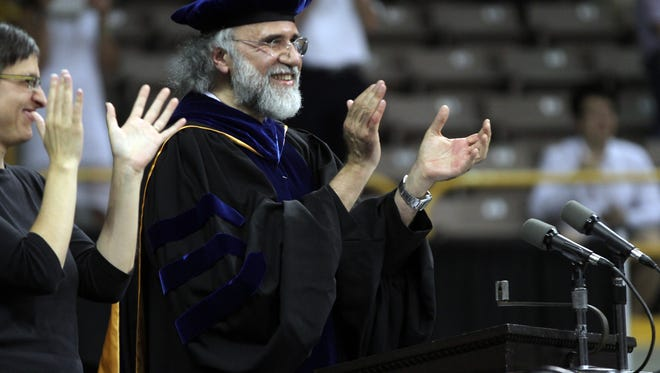 In this 2012 file photo, Chaden Djalali, dean of the University of Iowa College of Liberal Arts and Sciences, applauds graduates at Carver-Hawkeye Arena. Djalali announced recently that he will be stepping down as dean in 2018.