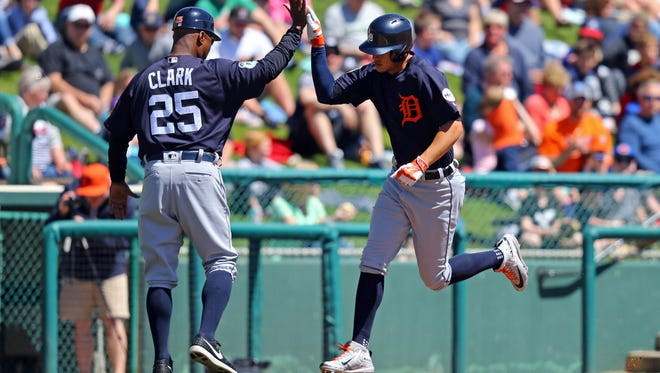 Tigers third base coach Dave Clark (25) high fives centerfielder JaCoby Jones (40) as he rounds third base after hitting a home run in the second inning at Champion Stadium. The Tigers won, 5-3.