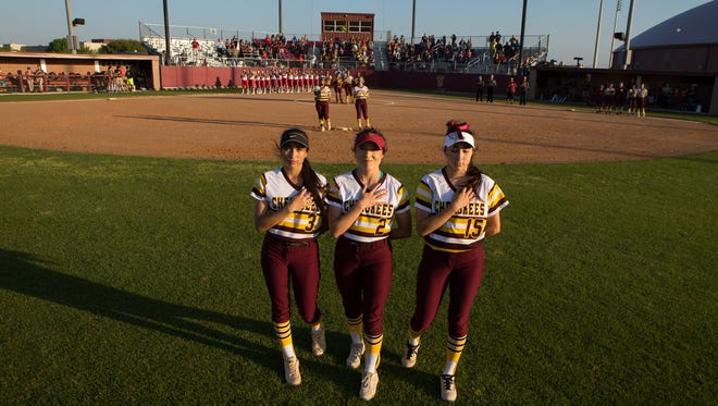 Tuloso-Midway's out fielders Evonne Valdez, Brisa Perez, and Celeste Valdez hold their hands over their harts for the National Anthem before their game against Veterans Memorial at Tuloso-Midway High School on Tuesday, March 21, 2017.