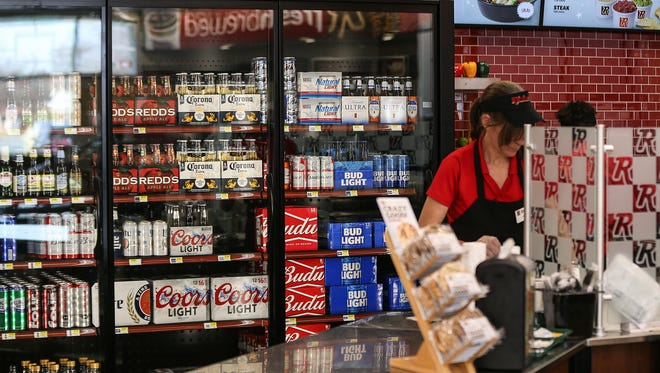 Cold beer is kept in coolers behind the counter at a Ricker's convenience store in Columbus, Ind., Thursday, March 23, 2017. Servers must bring the beer to a patron's table in the store's restaurant area. After the chain's lawyers realized the in-store restaurants qualified for cold beer sales, this Ricker's location and one in Sheridan, Ind., obtained the required licenses to serve cold beer to patrons for consumption in the restaurant or to-go. The Columbus location also sells liquor for consumption outside of the restaurant. To many in the liquor store industry, Ricker's use of this loophole seems like an attempt to cut into an area that has previously been domain of liquor stores, which are subject to additional regulations.