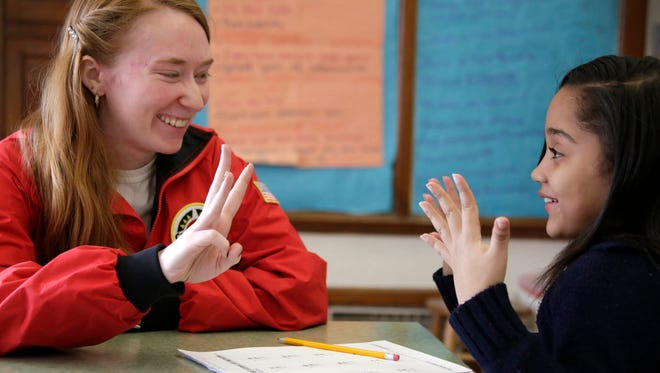 City Year program volunteer Taylor Bradley, 23, of Berkley, left, helps third grader Mariah Golden with her math at Mary McLeod Bethune Elementary school in Detroit on Thurs., March 23, 2017.