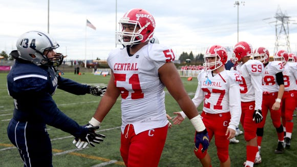 Central's Marlon Tuipulotu (51) and his teammates shake hands with Wilsonville players following the Central vs. Wilsonville OSAA Class 5A semifinal football game at Hillsboro Stadium on Saturday, Nov. 19, 2016. Wilsonville won the game 56-34.