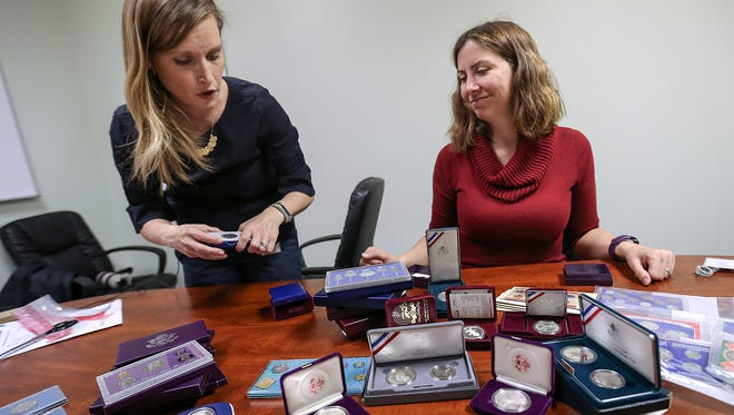 """From left, Lindsey Mayes and Valerie Jones spread out a large collection of coins, one of many items in the Attorney General's unclaimed property division """"vault,"""" in their southside office space, Thursday, April 6, 2017. Mayes is the director of the AG's unclaimed property division and Jones is project manager. The department houses physical property as well as unclaimed cash, stock and insurance payments, aiming to reunite property with its rightful owner."""