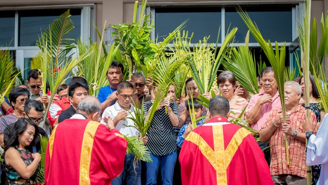 Churchgoers observe Palm Sunday at Santa Barbara Church in this April 9 file photo. Archbishop Michael Byrnes and priests throughout the island will celebrate Palm Sunday Masses without congregations physically present.