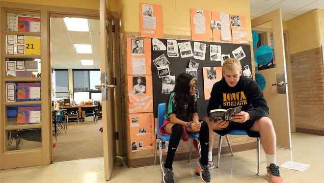 Twain Elementary sixth grader Maidenly Torres reads with Iowa long snapper Austin Spiewak on Tuesday, April 18, 2017.