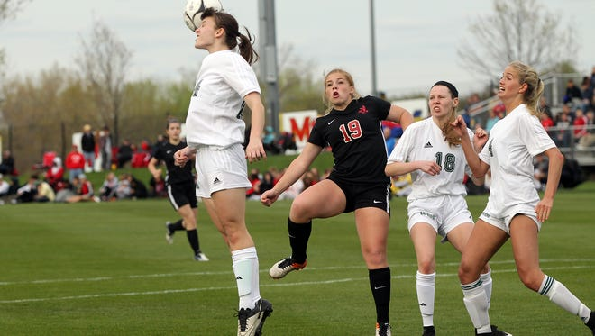 West High's Lexi Shaffer jumps for the ball during the Women of Troy's game against City High at the University of Iowa Soccer Complex on Friday, April 21, 2017. West High won, 2-0.