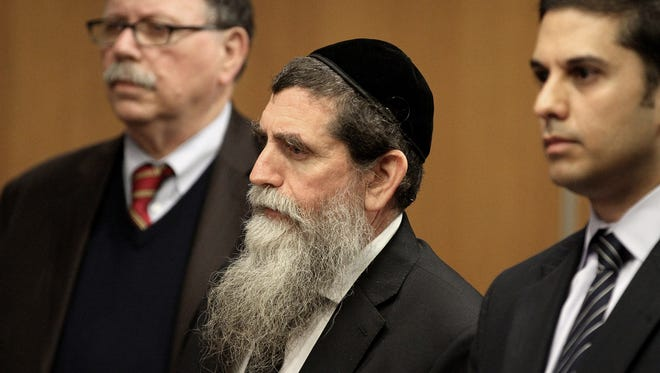 Rabbi Osher Eisemann, founder and director of Lakewood's SCHI school, is shown with attorneys during his arraignment at the Middlesex County Courthouse in New Brunswick Monday, April 24, 2017.