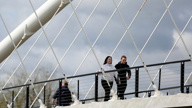 Rain clouds threaten as people walk across the Peter Courtney Minto Island Bridge over the Willamette River on April 28.