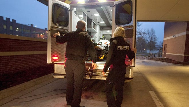 UCHealth PVH EMS Lt. Darin Johnson, PIO, left, and Chelsea Spencer, EMT, prepare to unload an empty gurney from their ambulance at the ambulance bay at Poudre Valley Hospital during the night shift on April 28, 2017.