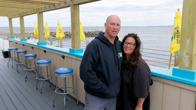 (right) Gigi Liaguno-Dorr, owner of Jakeabob's Bay, and her fiancé, (left) Wally VanOden, stand by the tiki bar at Jakeabob's Bay in Union Beach.