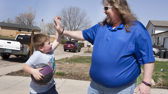 Brian Gary high fives his grandson, Zander, during a game of driveway basketball on a sunny March afternoon. Photo by Joel Blocker, For UCHealth.