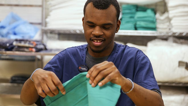 Malik Holland, 20, folds linens in the basement of Community Hospital North's surgery center, Friday, May 5, 2017. Holland is an intern in Project SEARCH, a program that provides educational and employment opportunities to high school seniors with disabilities.