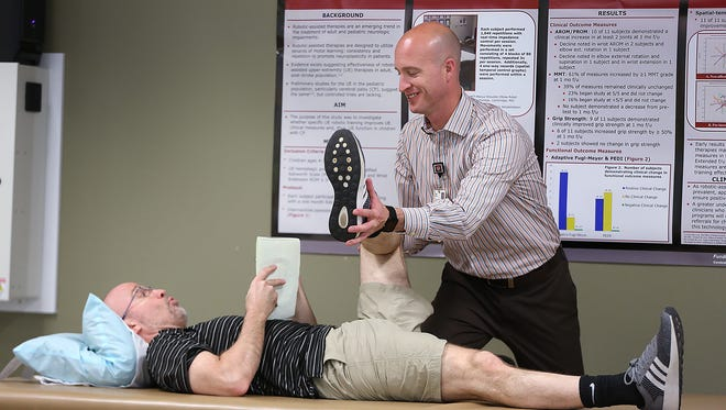 """IU Health Biomechanist Jeff Frame checks out IndyStar sports columnist Gregg Doyel's flexibility and pronounces him """"duck-footed."""""""