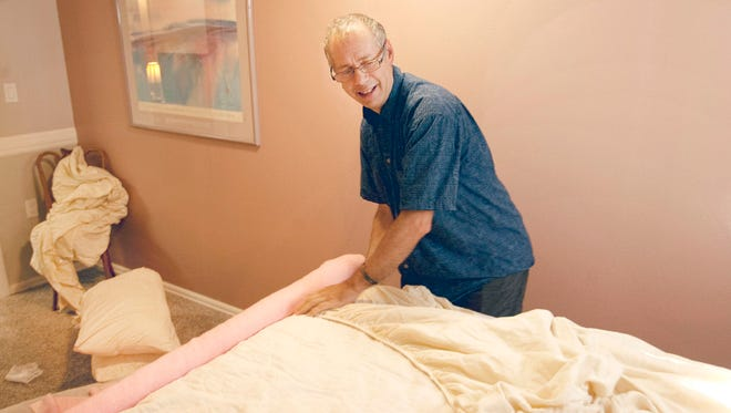 Gary Schmidt prepares a bedroom at his AirBnB in Loveland on Tuesday. Schmidt, a full-time piano teacher and performer who lives upstairs, said he prefers AirBnB to full-time renters.