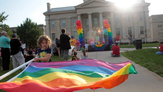 Christian Julian, 4, of iowa City waves a pride flag during a rally on the Pentacrest celebrating the Supreme Court's ruling on the Defense of Marriage Act on Wednesday, June 26, 2013.