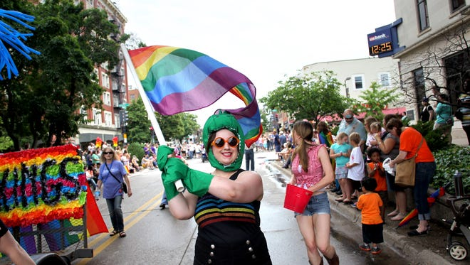 Katie Ferring heads down East Washington Street during the annual Iowa City Gay Pride Parade on Saturday, June 15, 2013. Benjamin Roberts / Iowa City Press-Citizen