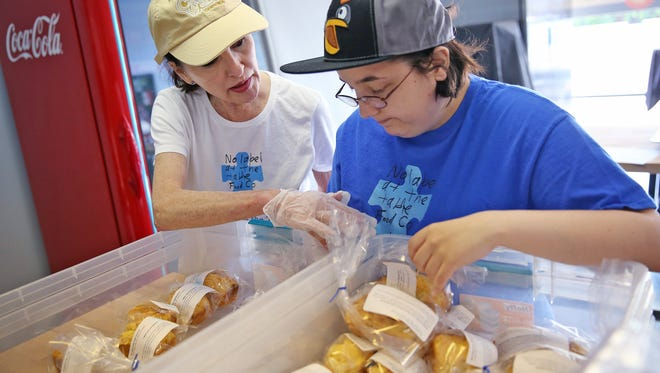 Volunteer Diane Laramore, left, works with Jessica Reed on labeling and packaging of food items on No Label at the Table's baking day, in Fishers, Friday, June 9, 2017.   No Label at the Table is a gluten/dairy-free food company whose mission is to give employment opportunities to people on the autism spectrum.  They also give job skills training to those employees.  Shelly Henley started the company with her son Jacob Wittman, who is on the spectrum.