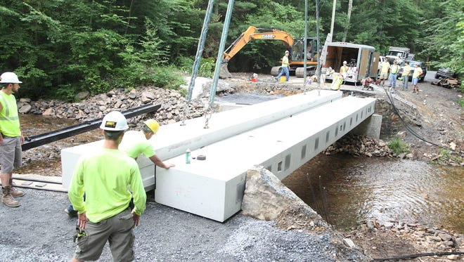 A crew installs concrete panels for a bridge on Old Forge Road, Quincy Township.