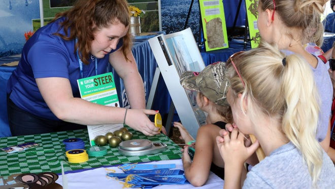 Alexa Roscizewski (left) helps children understand how much money it costs to raise cows at the UW-Extension tent at Farm Technology Days on July 12.