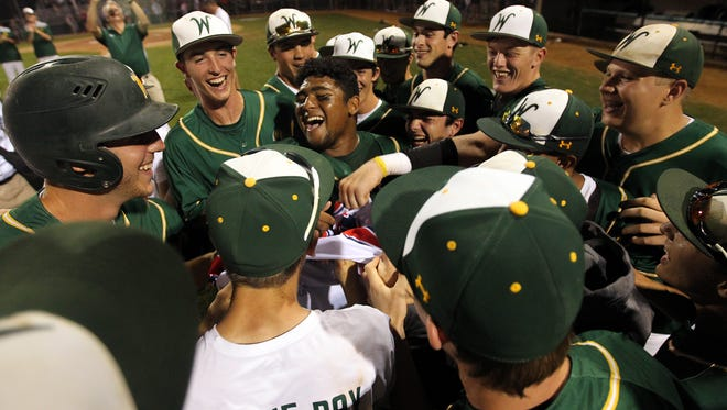 West High's Izaya Ono-Fullard, center, celebrates his walk-off grand slam as the Trojans beat Davenport West, 11-5, in five innings on Wednesday, July 19, 2017.