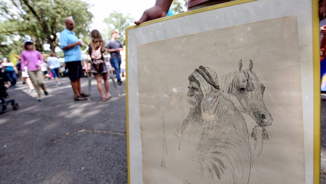 Sanford Webb, 52, of Portland, carries a Homer Davenport drawing he found at the thrift store during the Homer Davenport Days celebration in Silverton on Sunday, Aug. 7, 2016.