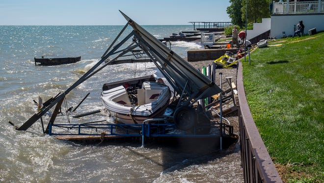 A destroyed 23-foot bowrider boat sits tangled in two boat hoists that blew over when a strong north wind blew in over Lake Huron Monday afternoon.