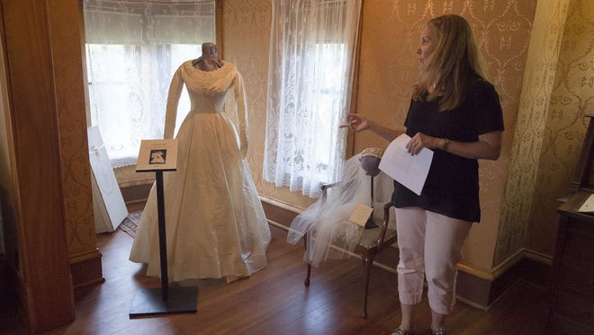 Poudre Landmarks Foundation costume committee chair Kimberly Miller points out Margaret Madsen Merrill's wedding gown Monday, July 24, 2017, at the historic Avery House in Fort Collins, Colo.