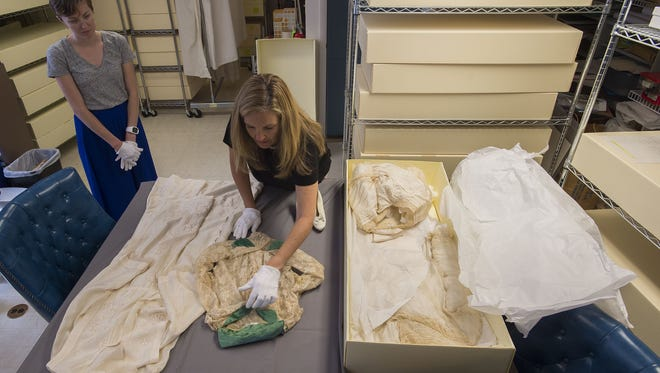 Poudre Landmarks Foundation costume committee chair Kimberly Miller, right, carefully lays out Mabel Avery's wedding dress while communication specialist Alison Sale looks on Monday, July 24, 2017, at the historic Avery House in Fort Collins, Colo.
