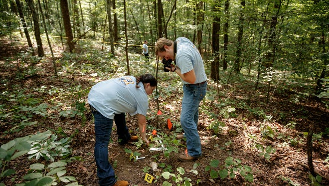 From left: Melanie Allen, of Milan, and Kelly Hendon, of Union City, both seniors at the University of Tennessee at Martin, are shown locating and photographing evidence during an exercise in the University of Tennessee Arboretum in Oak Ridge.