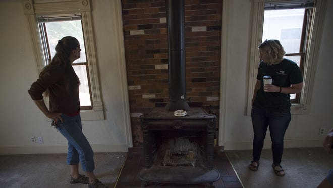 Mountain-n-Plains property management development director Stevie Robinett, right, and history blogger Meg Dunn look at a fireplace believed to be an add-on to the room, Friday, August 4, 2017, during a tour of Fort Collins' oldest still-inhabited home at 406 Stover Street in Fort Collins, Colo.